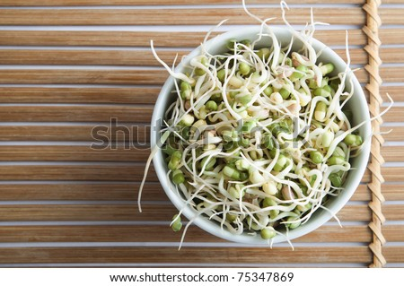 Overhead shot of a bowl of mung beansprouts, standing on a slatted bamboo mat. - stock photo