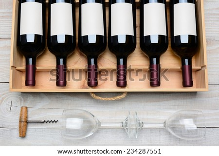 Overhead shot of a case of red wine bottles with blank labels  on a rustic white wood table with wine glasses and cork screw below. Horizontal format. - stock photo