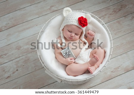 Overhead shot of a four month old baby girl wearing a white, crocheted bear hat with a red flower embellishment. She is sleeping in a wire basket and holding a tiny gift. - stock photo