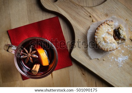 Overhead shot of a glass of mulled wine on red napkin, with partially eaten mince pie on wooden paddle board.  Light wood table below.