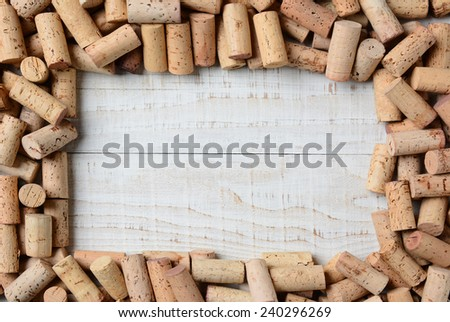 Overhead shot of a group of wine corks forming a frame on a rustic whitewashed wood table. Horizontal format.  - stock photo