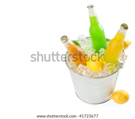 Overhead shot of a metal bucket full with ice cubes and three wet glass bottles with tropical fruit - stock photo