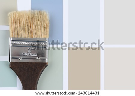 Overhead shot of  a paint brush with a brown handle laying on a sheet of color samples. Horizontal format with copy space. - stock photo