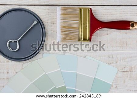 Overhead shot of  a paint can lid, opener, color samples and paint brush on a rustic wooden surface. Horizontal format with copy space.  - stock photo