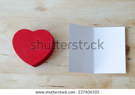 Overhead shot of a painted red wooden heart shaped gift box and an opened greeting card, left blank for a message. Both set on a light woodplank table.  - stock photo
