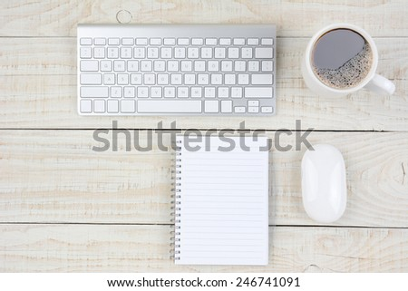 Overhead shot of a rustic white wood desk with keyboard, mouse, note pad, and coffee cup. Horizontal format with copy space. - stock photo