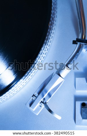 Overhead shot of a section of a record player. Photographed with blue lighting.