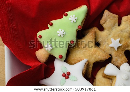 Overhead shot of a selection of home baked Christmas biscuits (cookies) with icing (frosting) and decorative elements.  Served in white square bowl with red napkin.