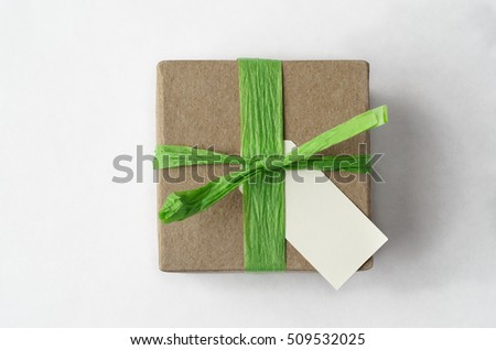Overhead shot of a simple brown gift box, with green raffia ribbon and blank label on white background.