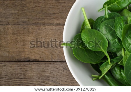 Overhead shot of a white bowl filled with fresh green raw spinach leaves, on an old oak wood planked table. - stock photo
