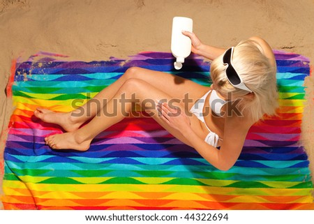 Overhead shot of a woman in a white bikini sitting on a beach towel applying suntan cream.
