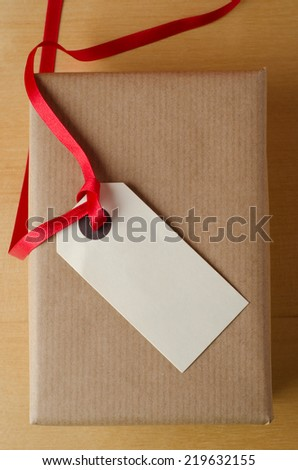 Overhead shot of a wrapped brown paper gift package on wood veneer table. Topped with a parcel tag and red ribbon, the blank label faces upwards to provide copy space for a message. - stock photo