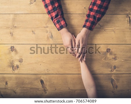 Overhead shot of a young man and woman holding hands on a wooden table