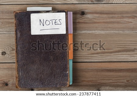 Overhead shot of an old brown notebook labeled with the word 'Notes' and updated with new tab dividers.  Laid on an old, weathered knotted wood plank table. - stock photo