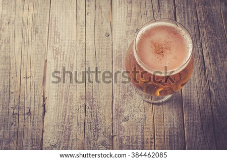 Overhead shot of beer glass on an old wooden table - stock photo
