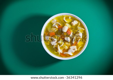 Overhead shot of bowl of soup on green table - stock photo