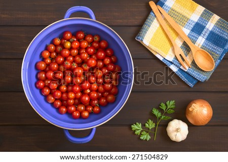 Overhead shot of cherry tomatoes in blue metal strainer with garlic, onion, parsley leaves and wooden cutlery on the side, photographed on dark wood with natural light