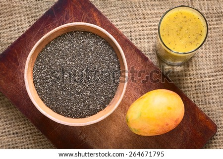 Overhead shot of chia seed (lat. Salvia hispanica) in bowl with mango and mango-chia juice photographed with natural light. Chia is considered a superfood with protein, omega fat, mineral, antioxidant - stock photo