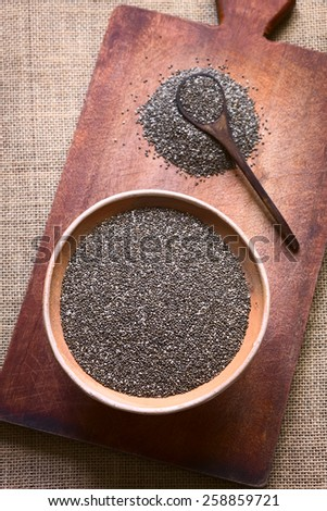 Overhead shot of chia seeds (lat. Salvia hispanica) in bowl photographed on wooden board with natural light. Chia seeds are considered a superfood (Selective Focus, Focus on the seeds in the bowl)