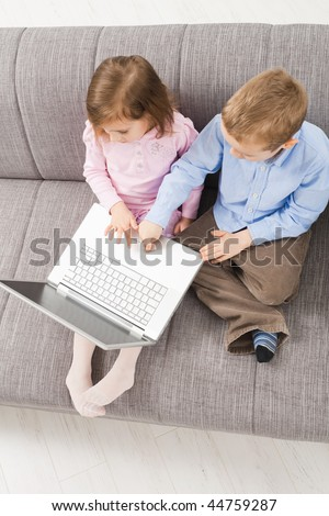 Overhead shot of children sitting on couch at home, browsing internet on laptop computer, looking at screen. - stock photo