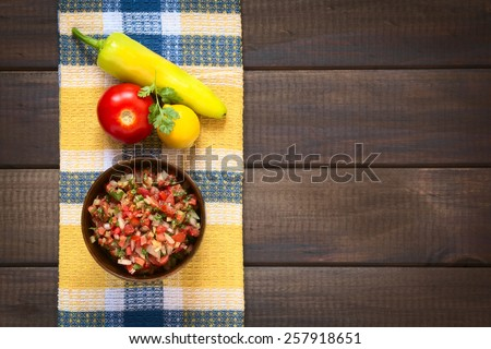 Overhead shot of Chilean Pebre sauce made of tomato, onion, aji verde (green hot pepper), lemon juice and coriander leaves served for barbecue and traditional dishes, photographed with natural light  - stock photo