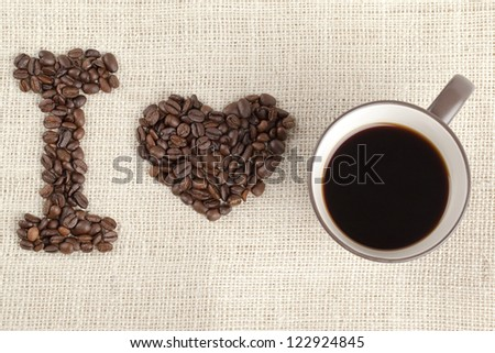 Overhead shot of coffee beans and coffee cup arranged to form I love you. - stock photo