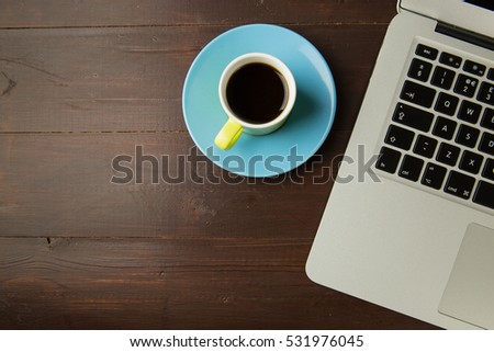 Overhead shot of coffee cup and laptop computer on brown wood office desk