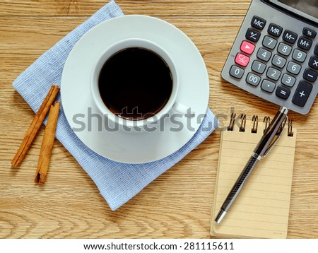 overhead shot of coffee cup, notebook, and calculator
