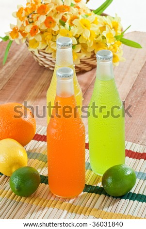 Overhead shot of cold drinks with fruits around them on wooden table - stock photo