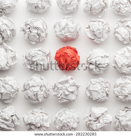 overhead shot of crumpled paper in oder and red one standing out. great idea concept on the white office table - stock photo