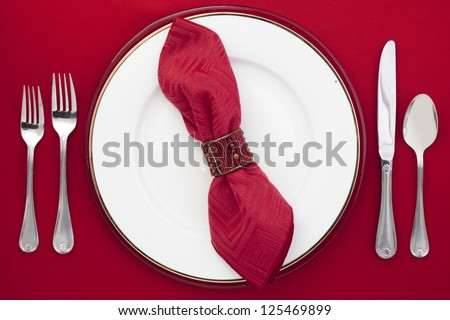 Overhead shot of dinner table setting on red table cloth. - stock photo