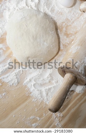 Overhead shot of dough and flour ona table with rolling-pin - stock photo