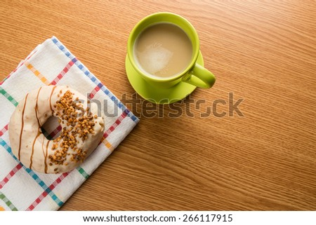 overhead shot of doughnut and coffee in green mug on table - stock photo