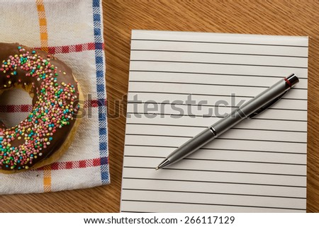 overhead shot of doughnut and notepad with pen on a table - stock photo
