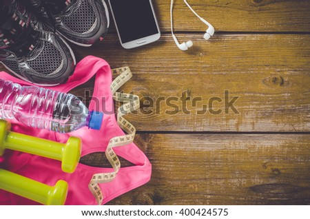 Overhead shot of female sport equipment on an old wooden table - stock photo