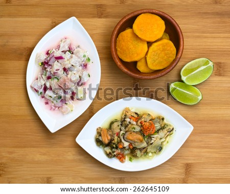 Overhead shot of fish and shellfish ceviche (raw fish and shellfish with red onion marinated in lime juice with garlic, salt and coriander) on wooden board, photographed with natural light - stock photo