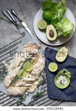 Overhead shot of fish baked in salt. Served with avocado and lime. - stock photo
