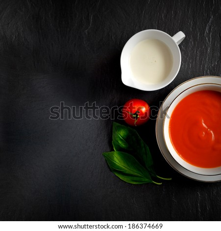 Overhead shot of fresh tomato soup with single cream, tomato and basil herbs. Selective lighting. Extended copy space version. - stock photo