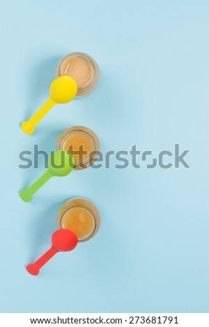 Overhead shot of glass jars of baby food with colorful spoons on blue background - stock photo