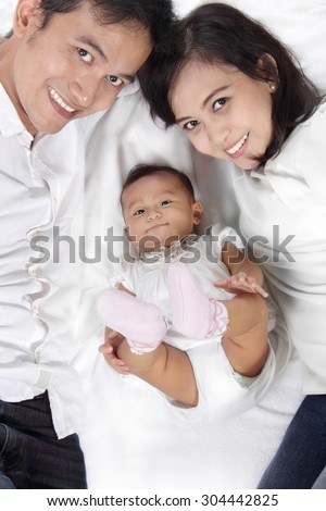 Overhead shot of happy small family laying on top of clean white bed sheet. Asian dad and mom with their cute little baby in the middle. - stock photo