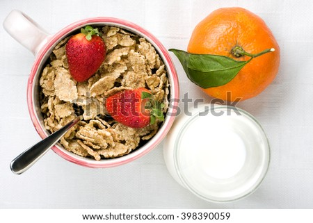 Overhead shot of nourishing breakfast with milk cup of cereal strawberries and mandarin orange