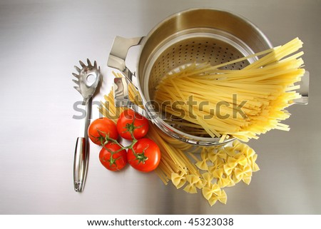Overhead shot of pasta, tomatoes and pot on stainless steel counter - stock photo
