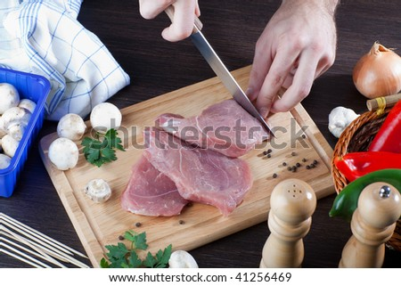 Overhead shot of person slicing raw pork meat on wooden bread board - stock photo