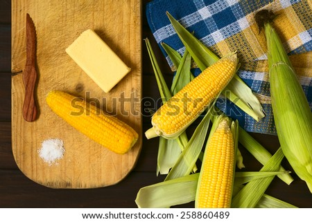 Overhead shot of raw and cooked sweet corn cobs, with butter and salt on wooden board, photographed with natural light - stock photo