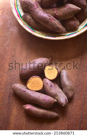 Overhead shot of raw purple sweet potato (lat. Ipomoea batatas) on wooden board photographed with natural light   - stock photo