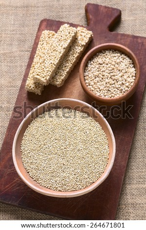 Overhead shot of raw white quinoa (lat. Chenopodium quinoa) grain seed, popped quinoa cereal, quinoa cereal bar on wood photographed with natural light (Selective Focus, Focus in middle of raw quinoa) - stock photo