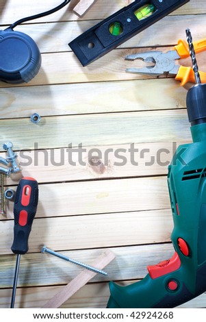 Overhead shot of screw driver, screws and drill on wooden table with empty space for your text - stock photo