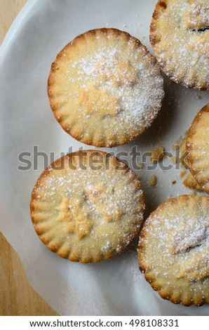 Overhead shot of several Christmas mince pies, dusted with icing sugar and arranged in a circle on a white plate.