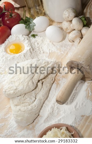 Overhead shot of table with dough and flour - stock photo