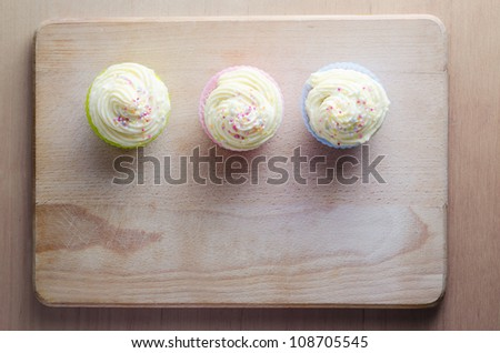 Overhead shot of three cupcakes on a wooden chopping board, topped with swirls of buttercream icing and colourful sprinkles. - stock photo